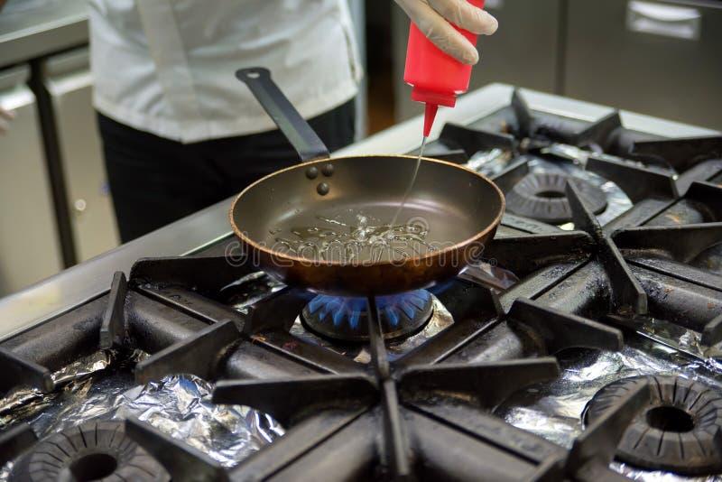倾吐的菜油到煎锅里 库存图片