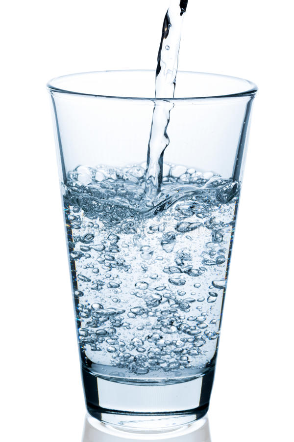倾吐的起泡的水到半满的玻璃里 免版税库存照片