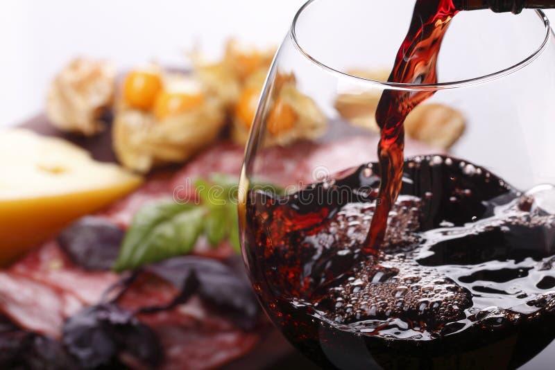 倾吐的酒到玻璃和食物里 免版税库存照片