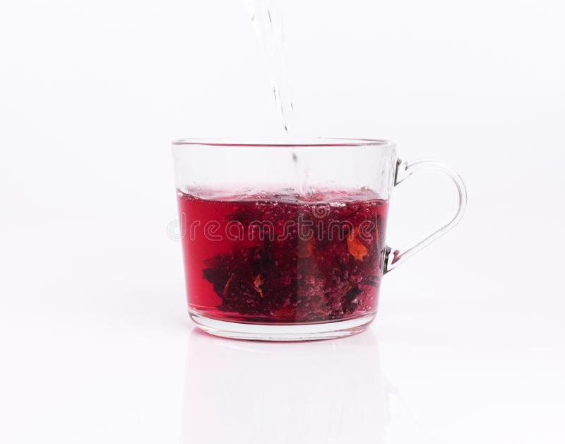 倾吐的面汤到玻璃杯子用木槿茶,隔绝在白色 库存照片