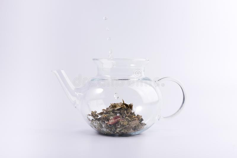 倾吐的面汤到玻璃茶壶用清凉茶,隔绝在白色 库存照片