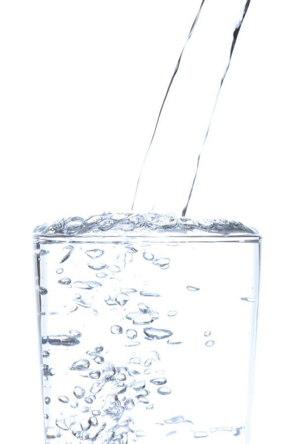 倾吐的饮用水到玻璃里有白色背景 免版税库存照片