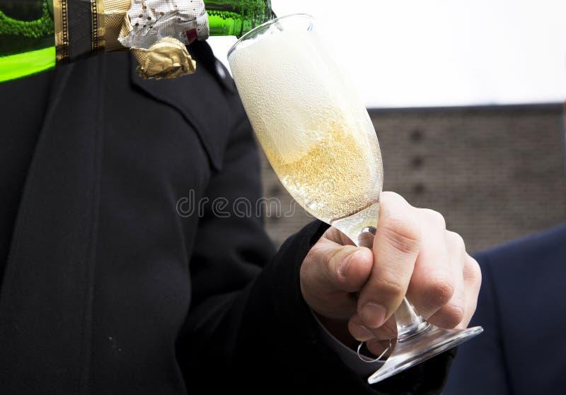 倾吐的香槟到玻璃里 免版税图库摄影
