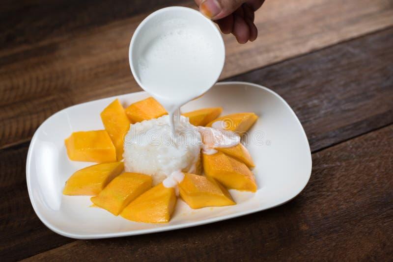 倾吐的cocunut挤奶在芒果黏米饭,一个传统泰国点心上 免版税库存图片