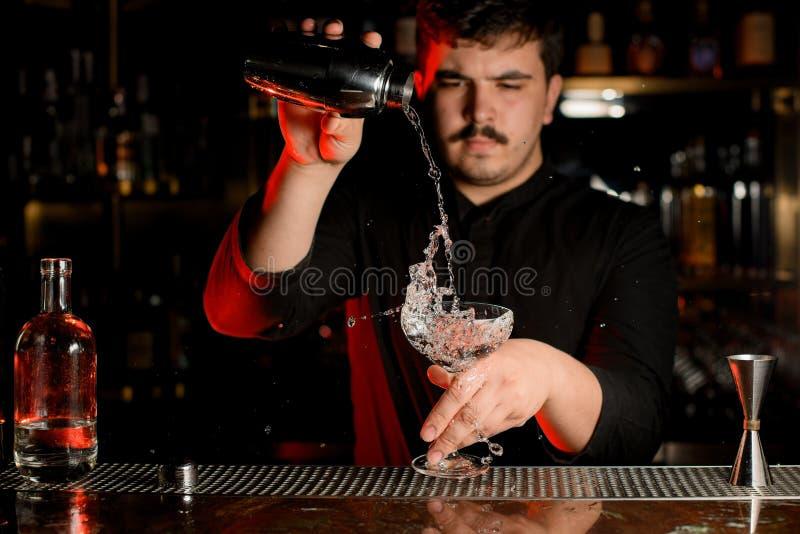 倾吐透明酒精的专业侍酒者入从振动器的鸡尾酒杯 库存照片