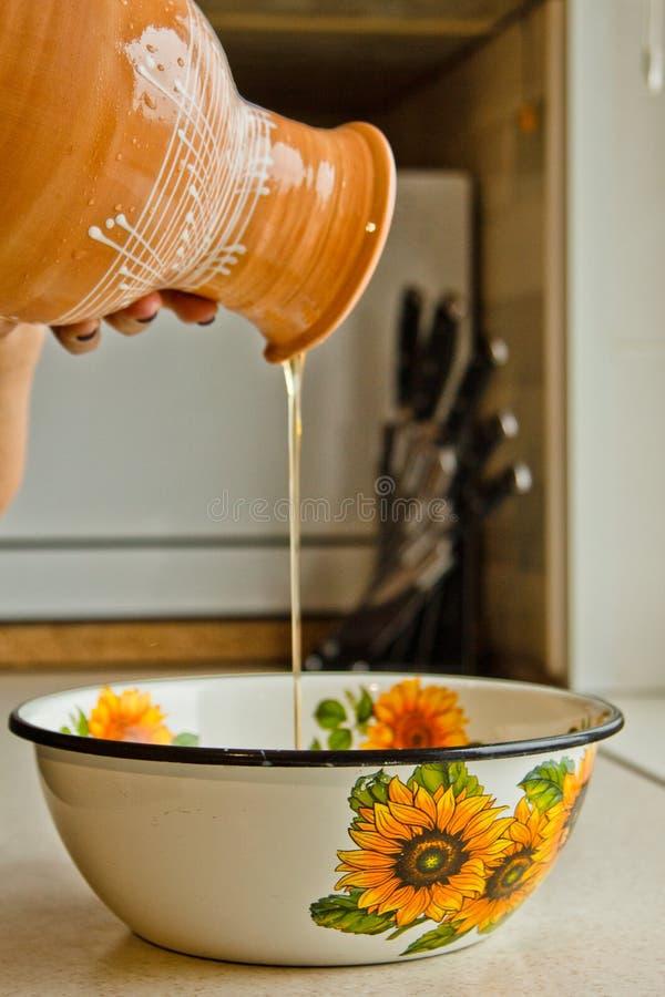 倾吐陶瓷大口水罐油的女性手入金属碗 绘在白色搪瓷,棕色陶器水罐特写镜头垂直 库存照片