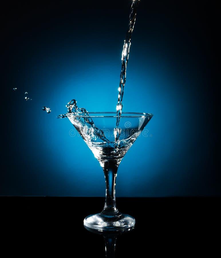 从倾吐马蒂尼鸡尾酒飞溅入玻璃 在蓝色背景的对象 免版税库存照片