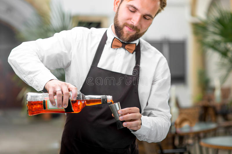 倾吐Aperol的男服务员 库存照片