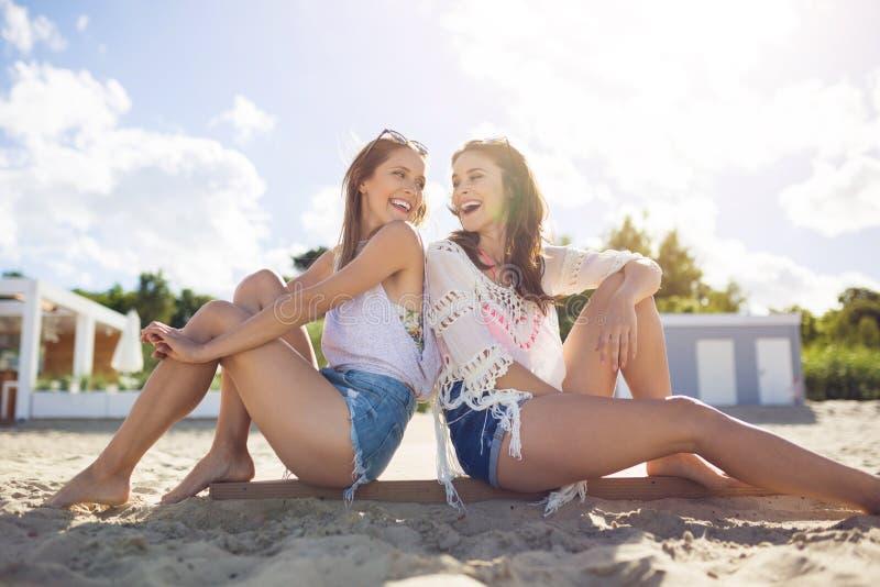 倾斜两个愉快的女性的朋友互相反对在beac支持 库存照片