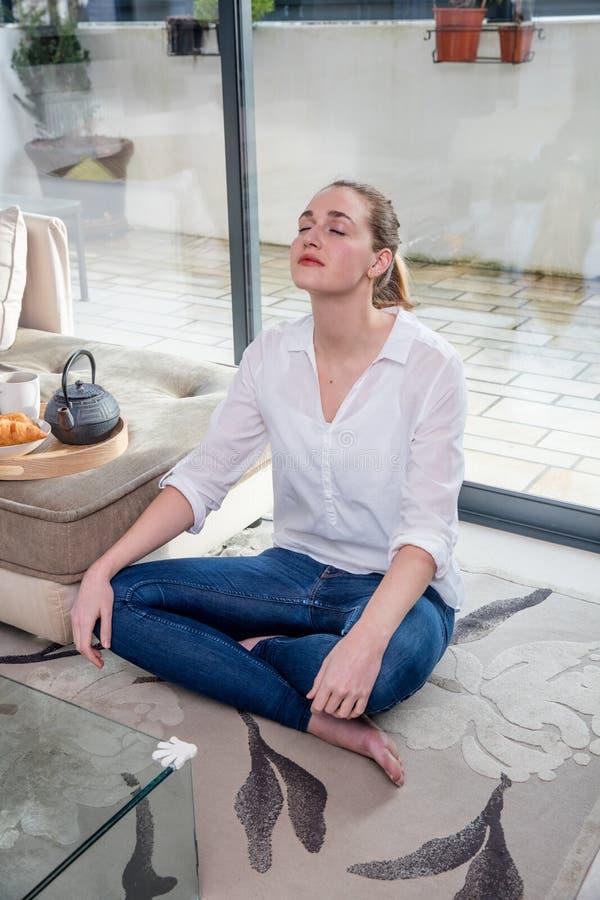 倾斜为早晨瑜伽和凝思的轻松的少妇 免版税库存图片
