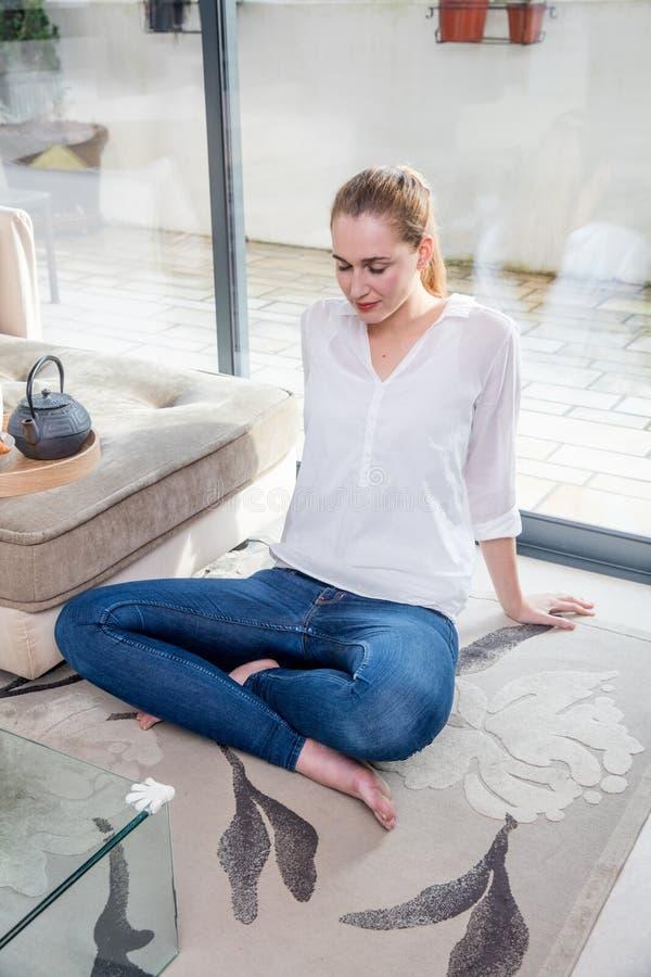 倾斜为早晨瑜伽实践的坦率的美丽的少妇 免版税库存照片