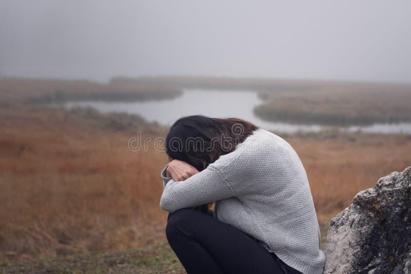 倾斜反对与胳膊的一块石头的少妇在面孔哭泣前面横渡了 库存图片