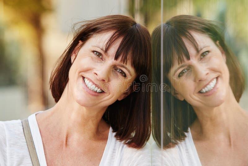 倾斜反对在大厦的反射的微笑的妇女 免版税库存图片