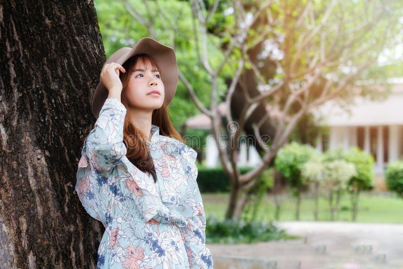 倾斜反对在树和放松的葡萄酒礼服的俏丽的亚裔女孩 库存图片