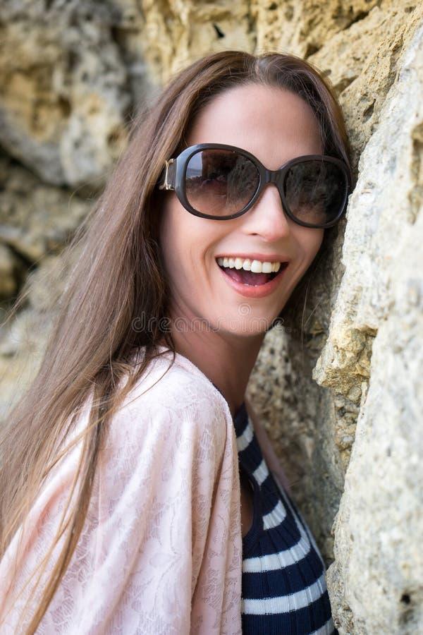 倾斜反对岩石微笑的美好的模型画象 免版税库存图片