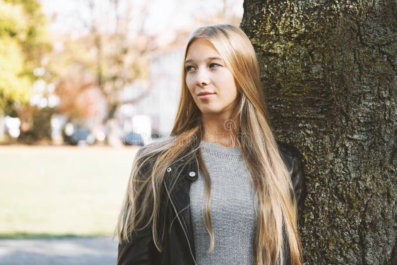 倾斜反对树的梦想的十几岁的女孩 免版税库存图片