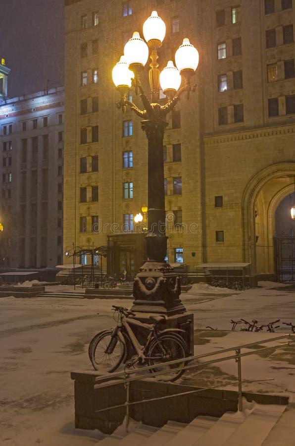 倾斜反对路灯柱的积雪的自行车 库存照片
