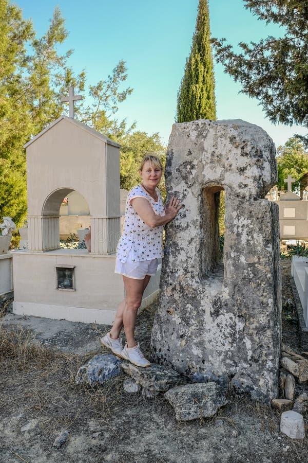 倾斜反对Monolythic医治用的石头的老妇人在g发现了 图库摄影
