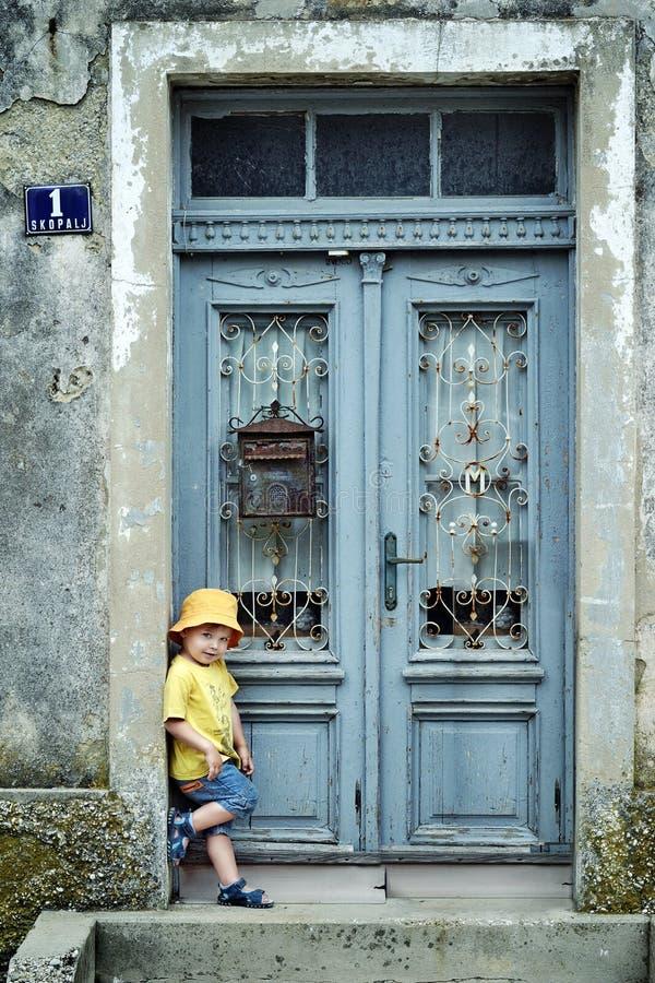 倾斜在一个减速火箭的门的一个逗人喜爱的小男孩的画象 库存照片