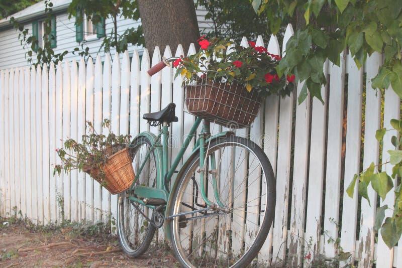 倾斜在一个白色尖桩篱栅的自行车 库存照片