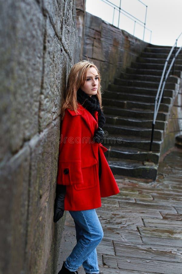 倾斜在一个老石墙的一件红色外套的妇女 免版税库存照片