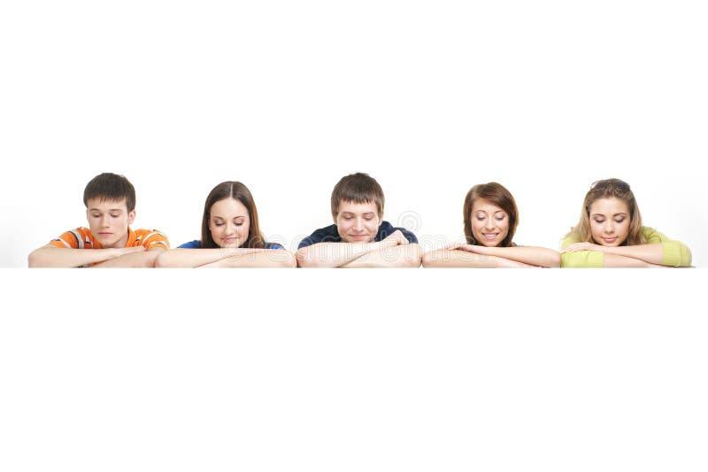 倾斜在一副空白横幅的一个组少年 免版税库存图片