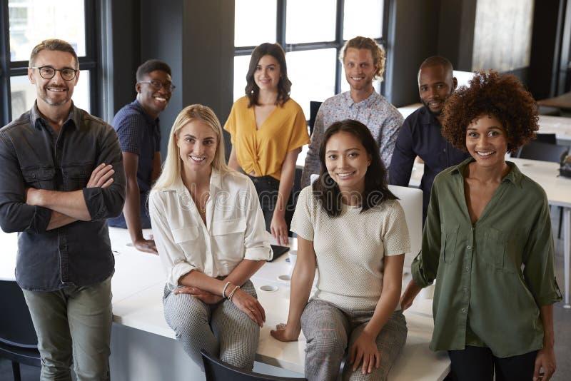 倾斜在书桌的一个创造性的企业队的画象,微笑对照相机在办公室,高的看法 免版税库存照片