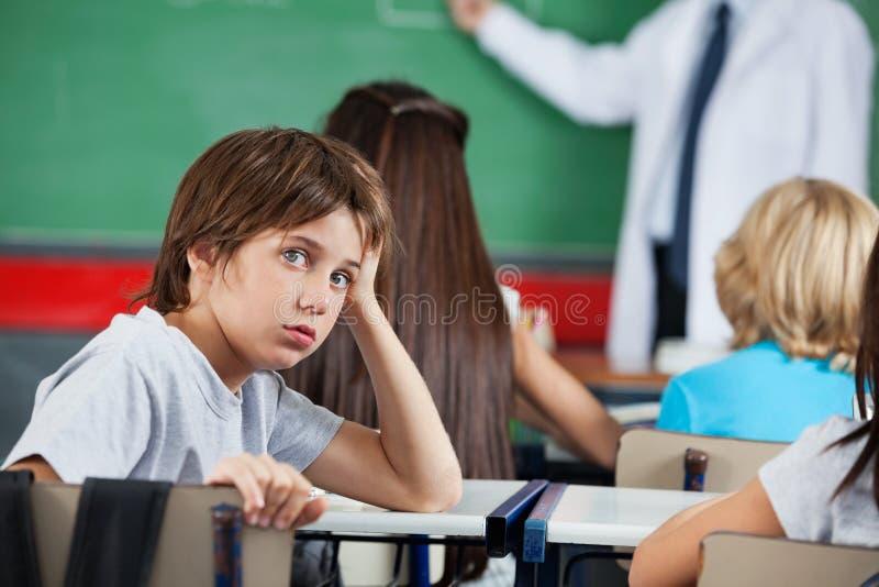 倾斜在书桌的小男孩画象 免版税库存图片