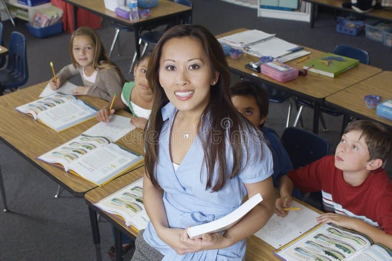 倾斜在书桌的老师,当看她时的学生 免版税库存图片