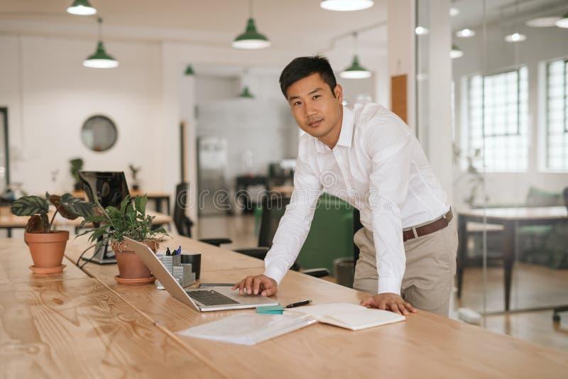 倾斜在他的书桌的年轻亚洲商人使用膝上型计算机 免版税库存照片