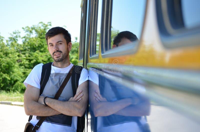 倾斜在公共汽车的年轻人 免版税库存图片
