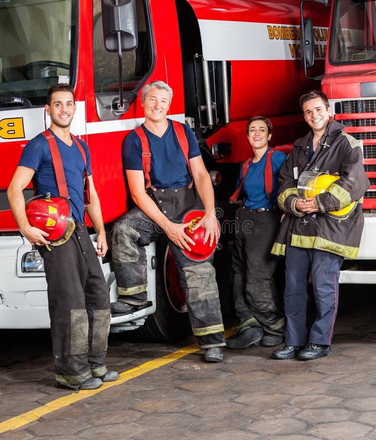 倾斜在卡车的微笑的消防队员画象  免版税库存图片
