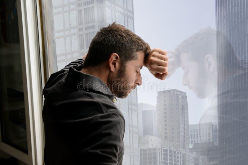 倾斜在商业区窗口的可爱的人遭受情感危机和消沉 库存照片