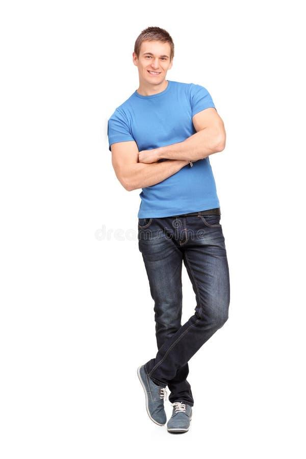 倾斜在墙壁的一个年轻人的全长纵向 库存图片