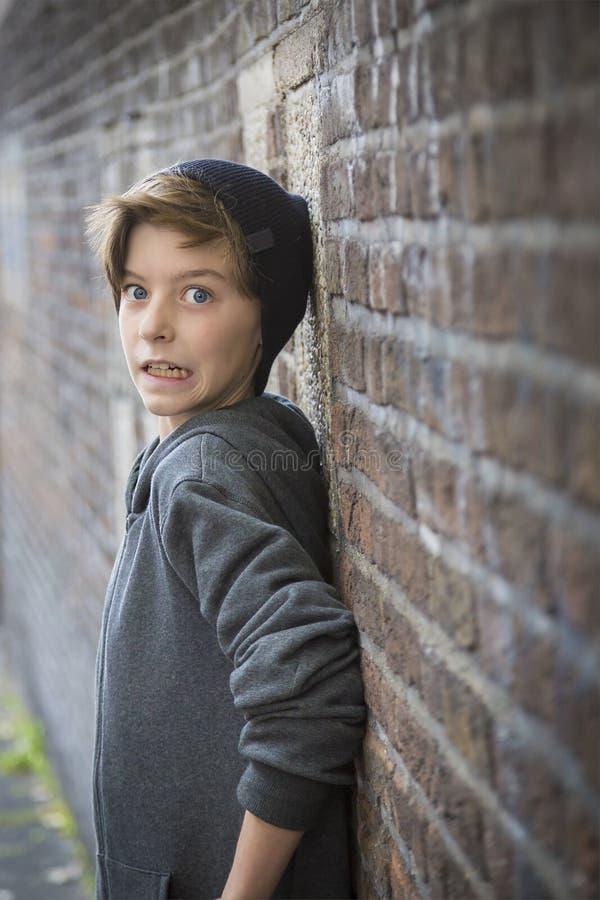 倾斜在墙壁的害怕的少年男孩 免版税库存图片