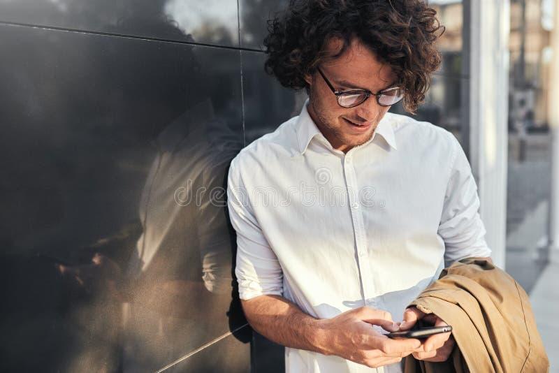 倾斜在墙壁的年轻英俊的商人,当站立户外和使用智能手机和自由无线时 有卷发的人 库存照片