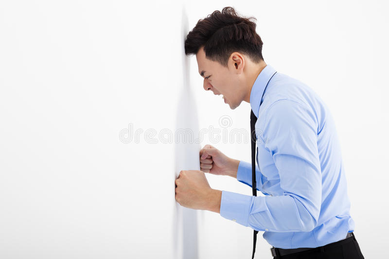 倾斜在墙壁的恼怒的年轻商人在办公室 库存照片