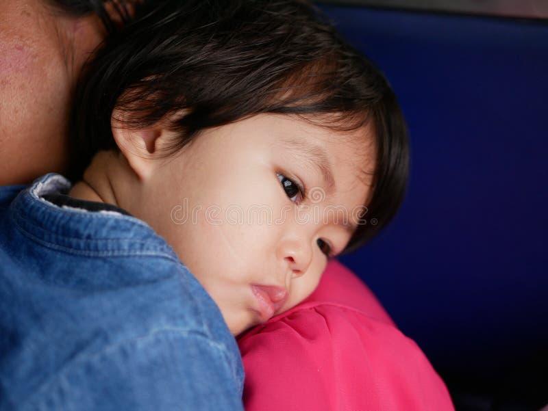 倾斜在她的母亲` s肩膀的小亚裔女婴 免版税图库摄影