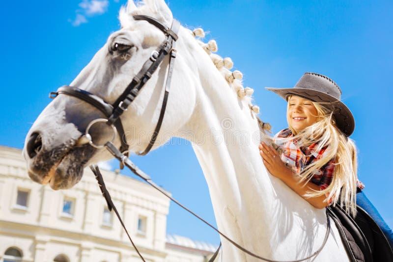 倾斜在她的白色赛马的微笑的逗人喜爱的牛仔女孩 免版税库存照片