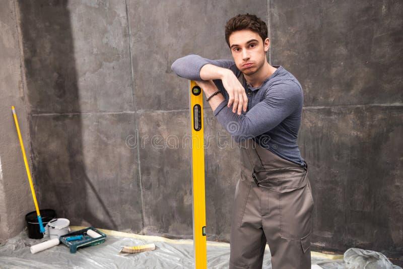倾斜在平实工具和看照相机的英俊的年轻工人 免版税图库摄影