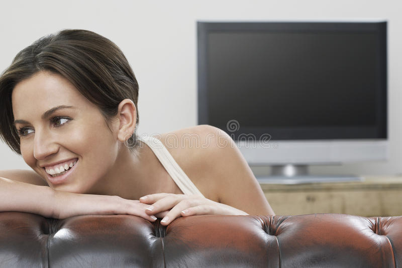 倾斜在有电视的沙发的愉快的妇女在背景中 库存图片