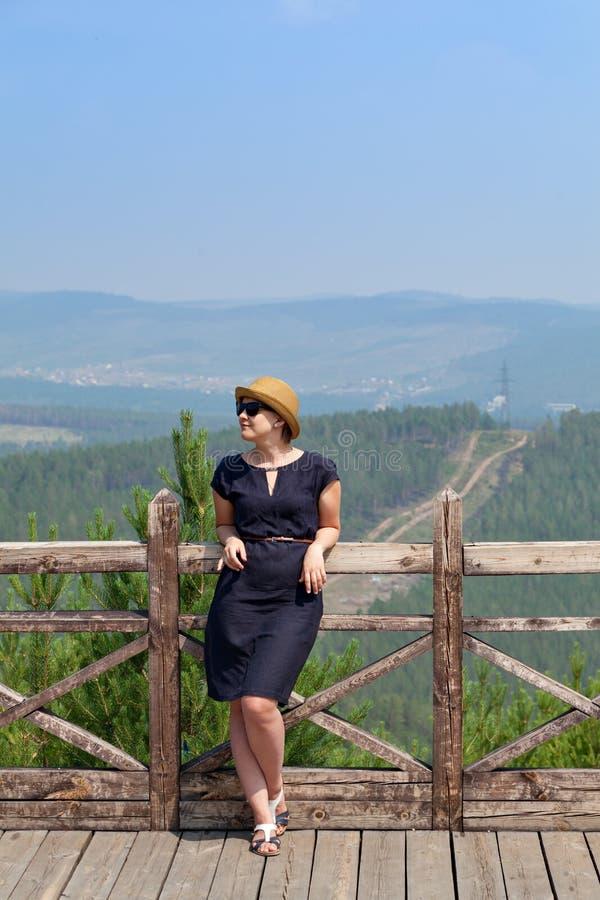 倾斜在木扶手栏杆的妇女 库存照片