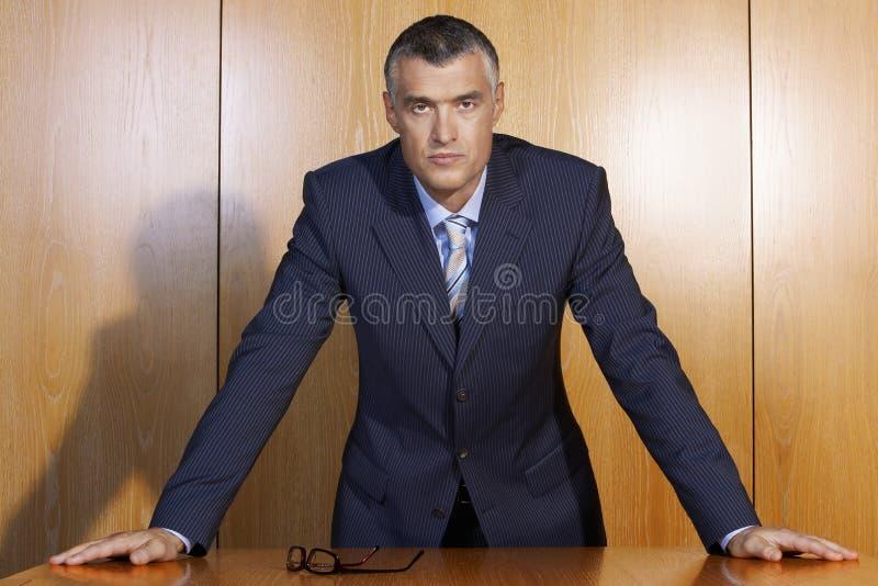倾斜在木表上的确信的商人 免版税库存照片
