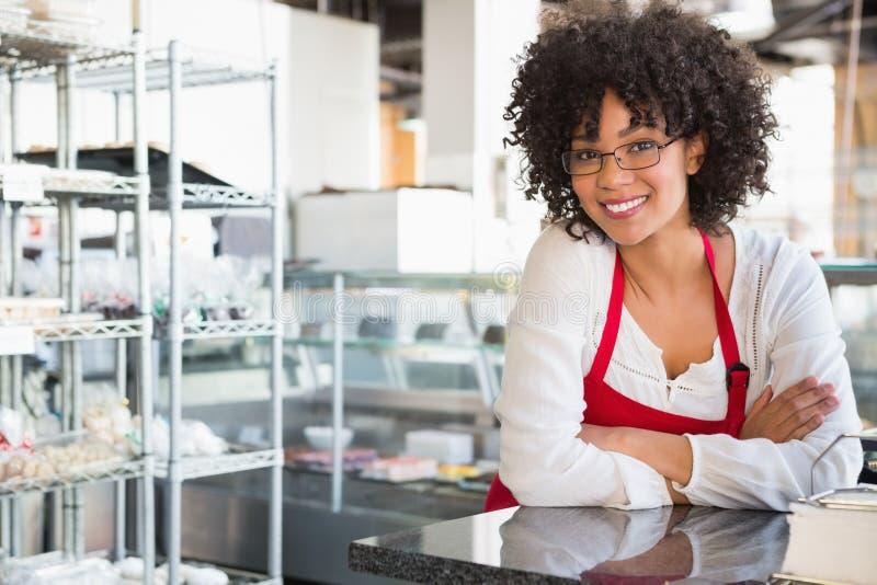 戴倾斜在柜台的眼镜的微笑的女服务员 库存照片