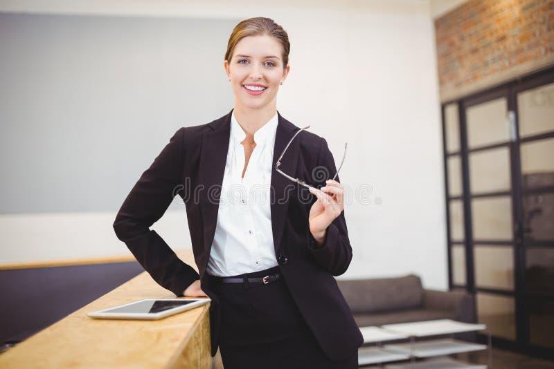 倾斜在柜台的美丽的女实业家 库存图片