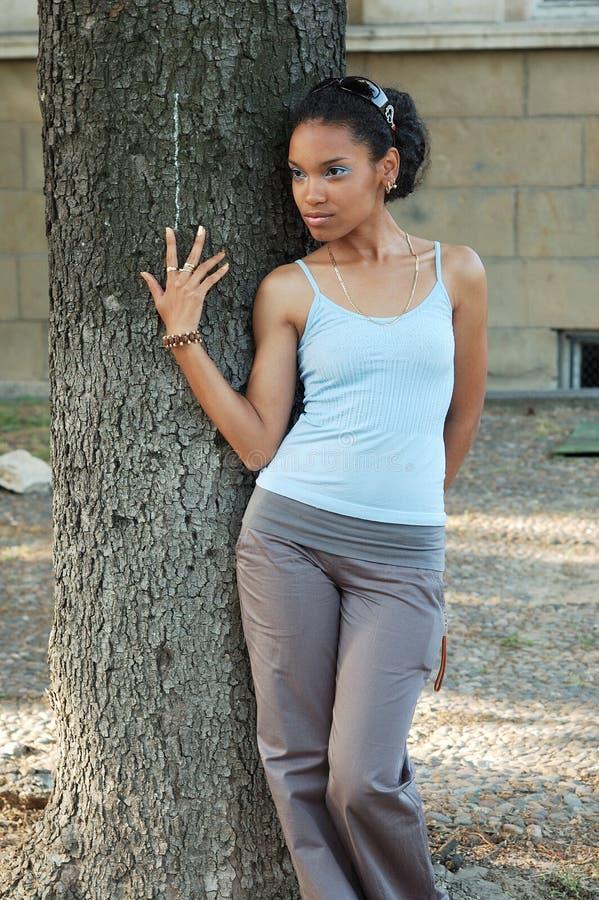 倾斜在树干的女孩 免版税库存图片