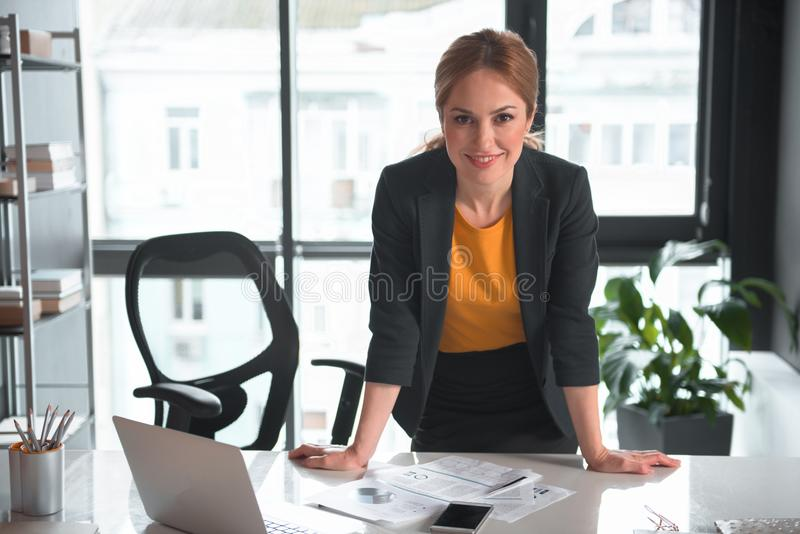倾斜在桌的快乐的女实业家 免版税库存照片