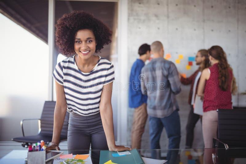 倾斜在桌的确信的女实业家,当队谈论在创造性的办公室时 库存照片