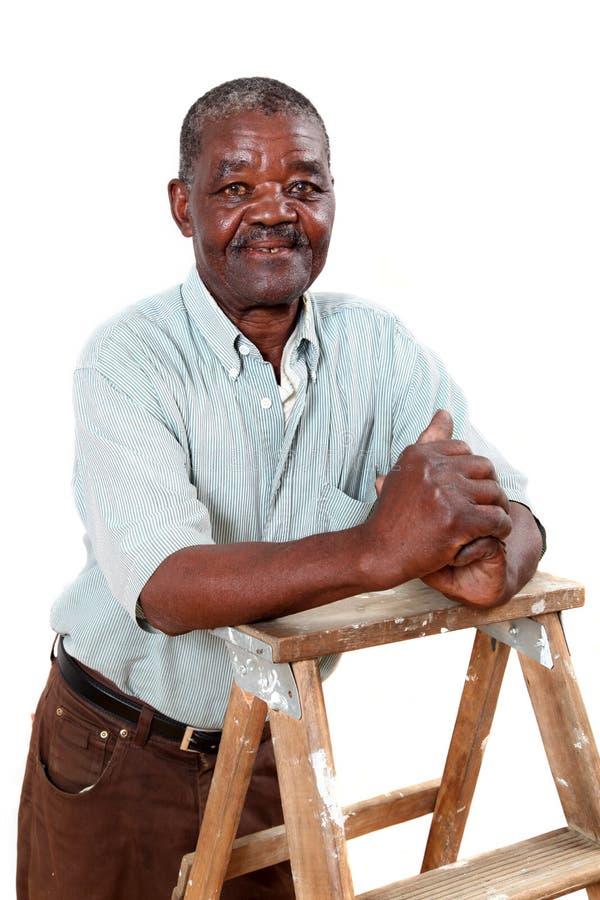 倾斜在梯子的老非洲人 库存照片