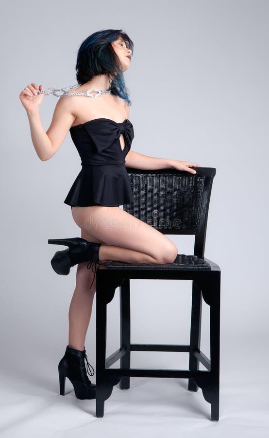 倾斜在椅子的一件的妇女 免版税库存照片